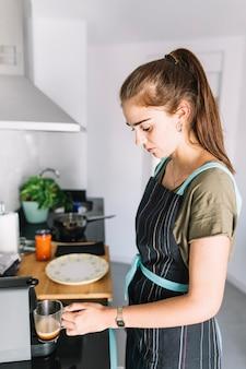 Jonge vrouw met glazen beker in het koffiezetapparaat