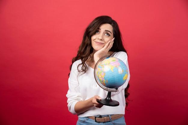 Jonge vrouw met globe dromen over reizen op rode achtergrond. hoge kwaliteit foto