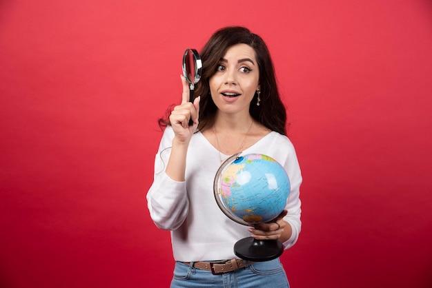 Jonge vrouw met globe en vergrootglas. hoge kwaliteit foto