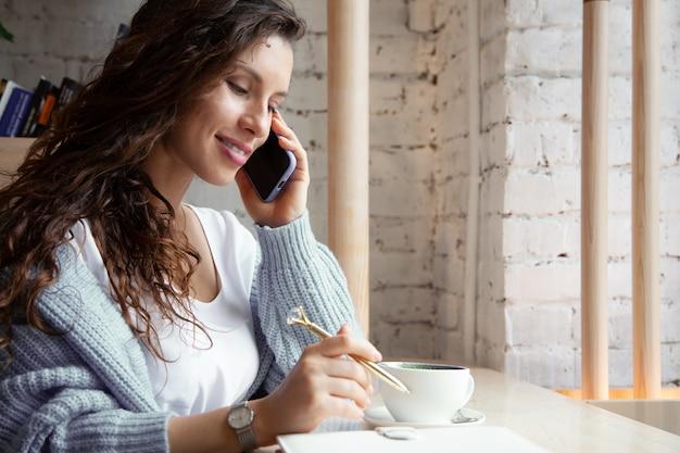 Jonge vrouw met golvend haar in warme blauwe gebreide trui praat aan de telefoon en het schrijven van notities tijdens het drinken van gezonde hete blauwe koffie latte gemaakt van natuurlijke vlindererwtthee. schoonheid en welzijn