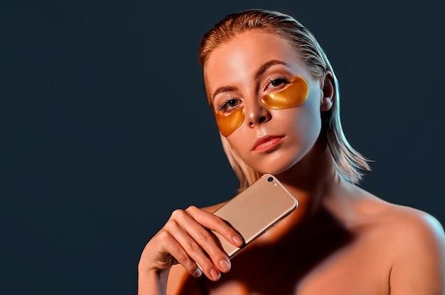 Jonge vrouw met gouden ogen patches en telefoon in de hand