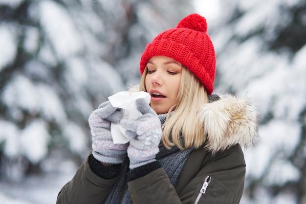 Jonge vrouw met griep en haar neus snuiten bij zakdoek