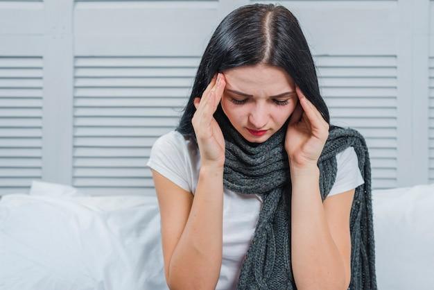 Jonge vrouw met grijze sjaal rond haar nek met hoofdpijn aan haar hoofd te raken