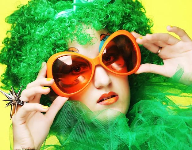 Jonge vrouw met groen haar en carnavalglazen