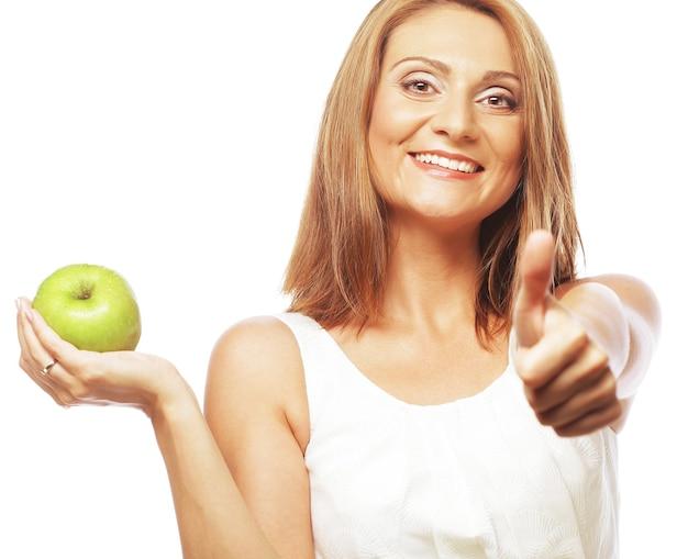 Jonge vrouw met groene appel en duim opdagen