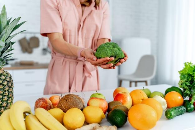 Jonge vrouw met groenten die broccoli in handen houden die op de keuken koken. tabel met gezonde voeding. bijgesneden foto.