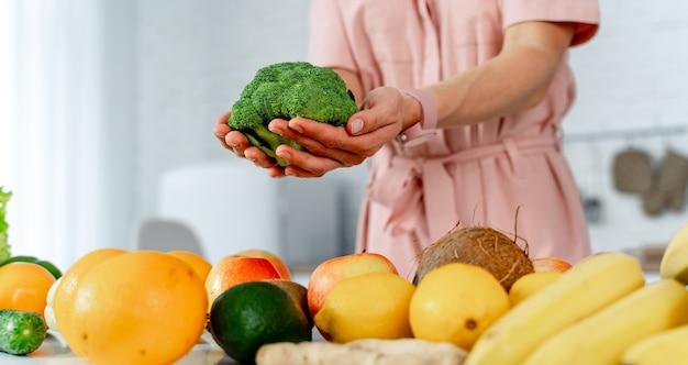 Jonge vrouw met groenten die broccoli in handen houden die op de keuken koken