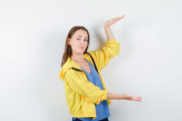 Jonge vrouw met groot formaat bord in t-shirt, jas en zelfverzekerd, vooraanzicht.