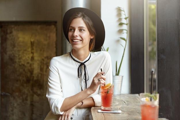 Jonge vrouw met grote hoed in café
