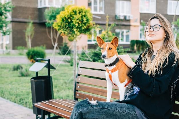 Jonge vrouw met haar basenji-hond zittend op een bankje in het stadspark.