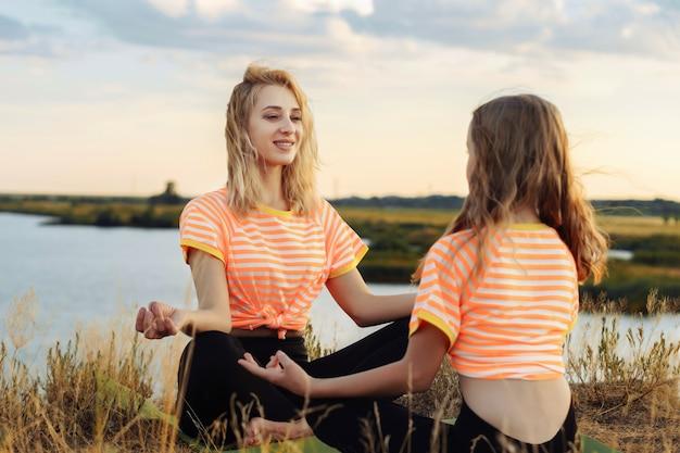 Jonge vrouw met haar dochter die yoga buiten maakt