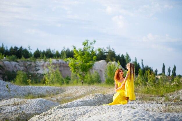 Jonge vrouw met haar dochter in een gele jurk in de buurt van het meer met azuurblauw water en groene bomen. gelukkig familie relatie concept