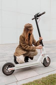 Jonge vrouw met haar elektrische scooter