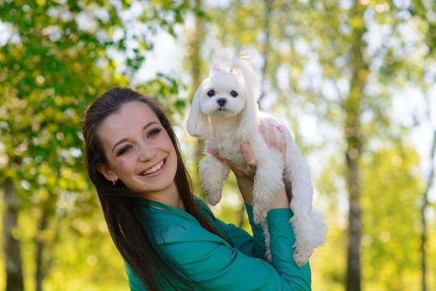 Jonge vrouw met haar hond. puppy witte hond met zijn eigenaar. concept over vriendschap, dier en vrijheid.