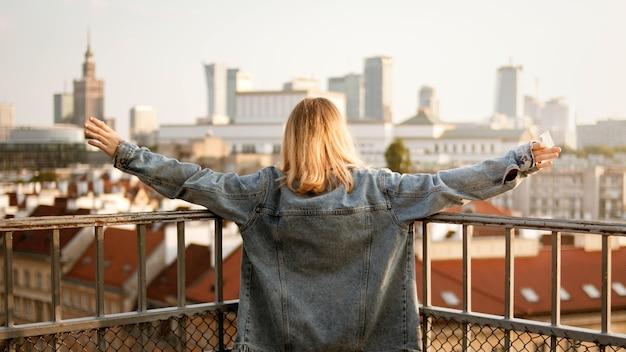 Jonge vrouw met haar open armen en de stadsgebouwen