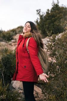 Jonge vrouw met haar rugzak die van verse lucht in de berg genieten