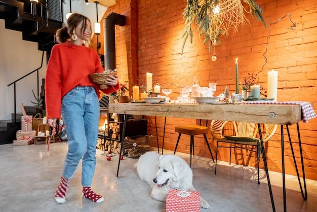 Jonge vrouw met haar schattige hond die zich voorbereidt op een nieuwjaarsvakantie bij de open haard en eettafel thuis
