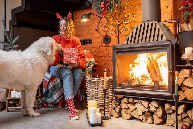 Jonge vrouw met haar schattige witte hond tijdens een gelukkig nieuwjaarsvakantie die thuis bij een open haard zit