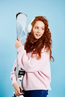 Jonge vrouw met haar ski's die exemplaarruimte bekijken