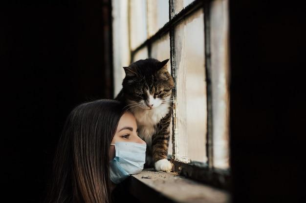 Jonge vrouw met haar trieste kat, om thuis te zitten tijdens coronavirusquarantaine.