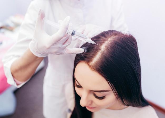 Jonge vrouw met haaruitval probleem injectie ontvangen, close-up