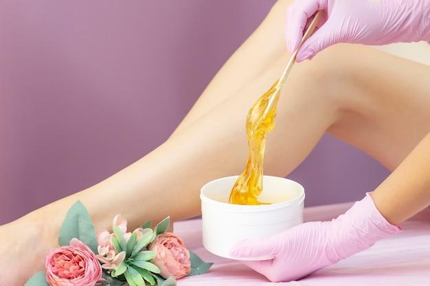 Jonge vrouw met haarverwijderingsprocedure op been met suikerpasta in salon