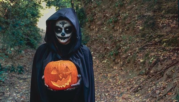 Jonge vrouw met halloween-het masker van het verfgezicht die zwarte kap dragen