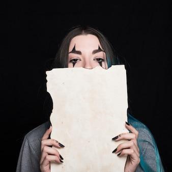 Jonge vrouw met halloween-make-up die stuk van document houdt