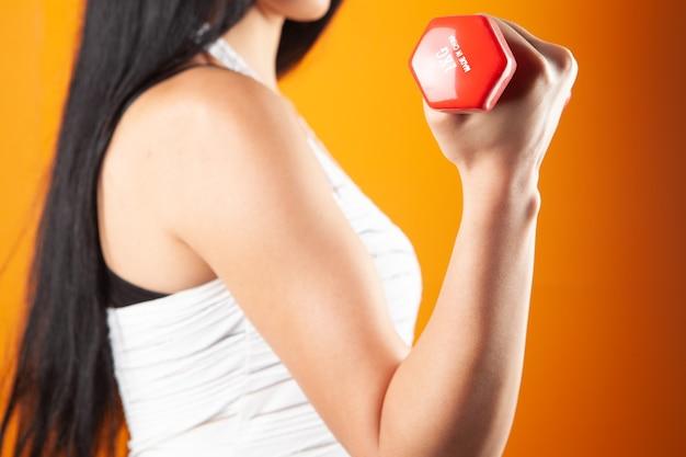 Jonge vrouw met halters op oranje achtergrond