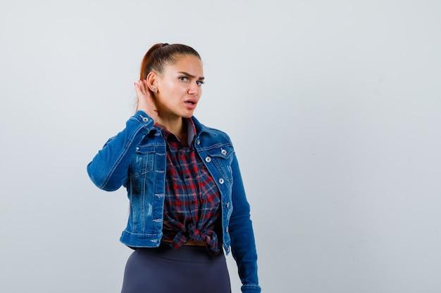Jonge vrouw met hand achter oor in geruit overhemd, jeansjasje en weemoedig, vooraanzicht.