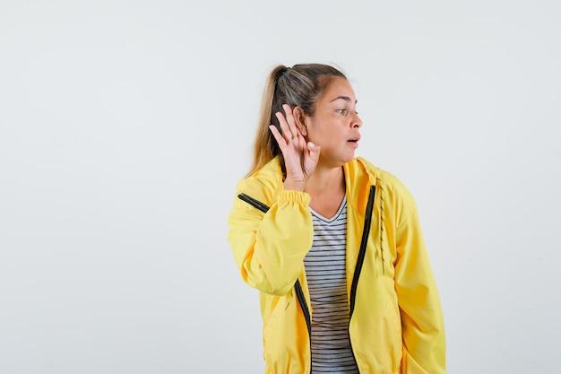 Jonge vrouw met hand achter oor in t-shirt, jasje en op zoek nieuwsgierig, vooraanzicht.