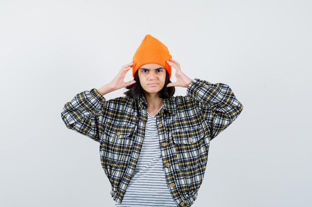 Jonge vrouw met hand in de buurt van hoofd in oranje hoed geruit hemd ziet er ontevreden uit