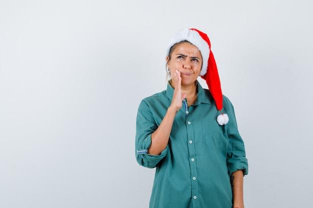 Jonge vrouw met hand in de buurt van mond, opzoeken in shirt, kerstmuts en attent, vooraanzicht.