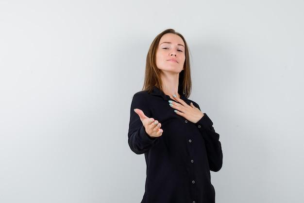 Jonge vrouw met hand op borst