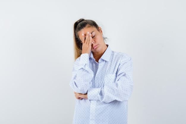 Jonge vrouw met hand op gezicht in wit overhemd en op zoek gestrest