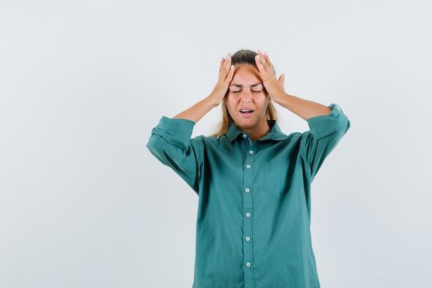 Jonge vrouw met hand op haar hoofd in blauw shirt en op zoek stressvol