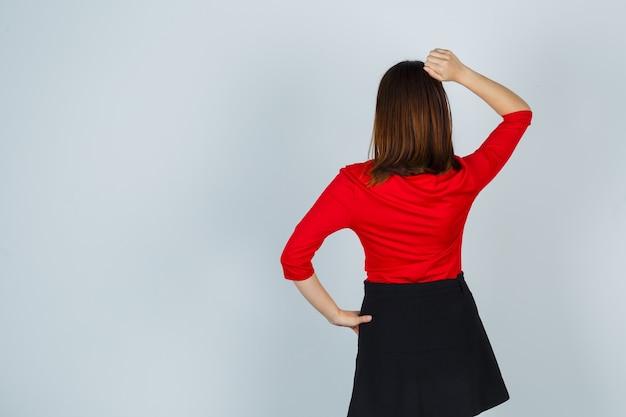 Jonge vrouw met hand op heup, hand zetten hoofd in rode blouse