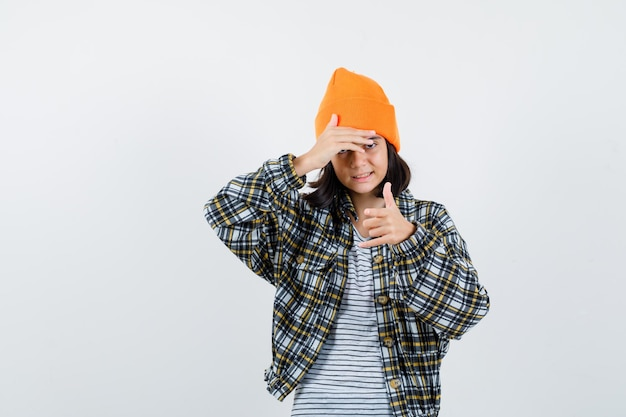 Jonge vrouw met hand op hoofd in oranje hoed en geruit hemd die er ontevreden uitziet