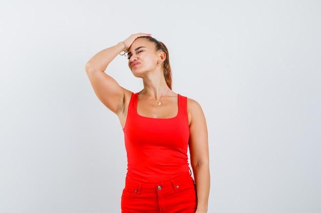 Jonge vrouw met hand op hoofd in rood mouwloos onderhemd, broek en op zoek pijnlijk, vooraanzicht.
