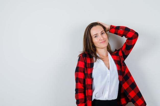 Jonge vrouw met hand op hoofd in vrijetijdskleding. vooraanzicht.
