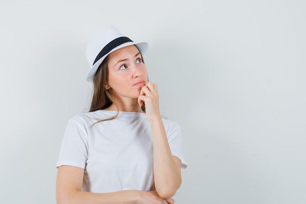 Jonge vrouw met hand op kin in wit t-shirt, hoed en op zoek attent.