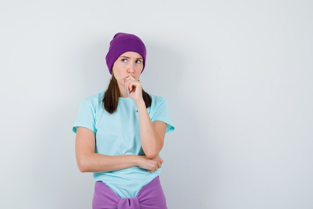 Jonge vrouw met hand op mond, denkend aan iets in blauw t-shirt, paarse muts en peinzend kijkend. vooraanzicht.