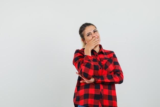 Jonge vrouw met hand op mond in ingecheckte shirt en op zoek sorry. vooraanzicht.