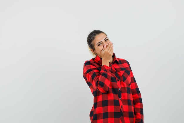 Jonge vrouw met hand op mond terwijl lachen in ingecheckte shirt vooraanzicht.