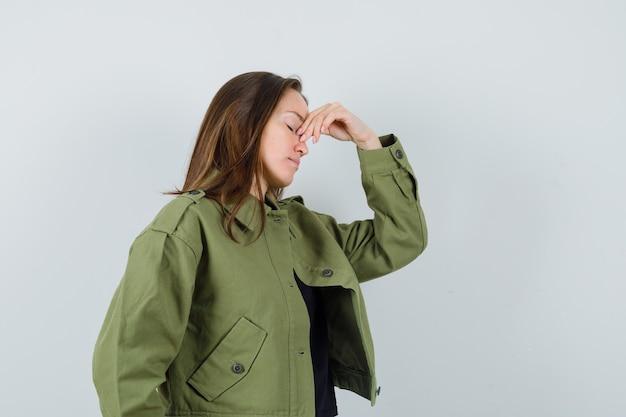 Jonge vrouw met hand op neus in groene jas en op zoek verveeld. vooraanzicht.