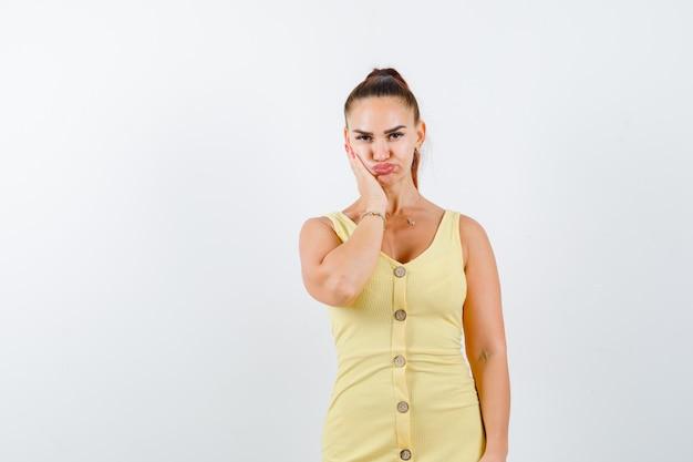 Jonge vrouw met hand op wang in gele jurk en teleurgesteld op zoek