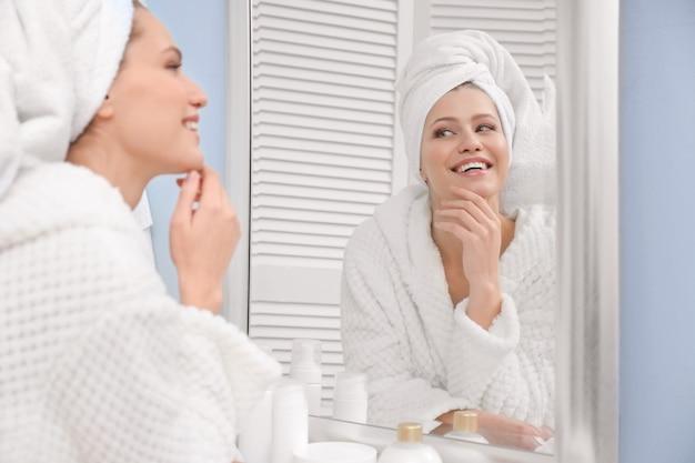 Jonge vrouw met handdoek die thuis in de spiegel naar zichzelf kijkt