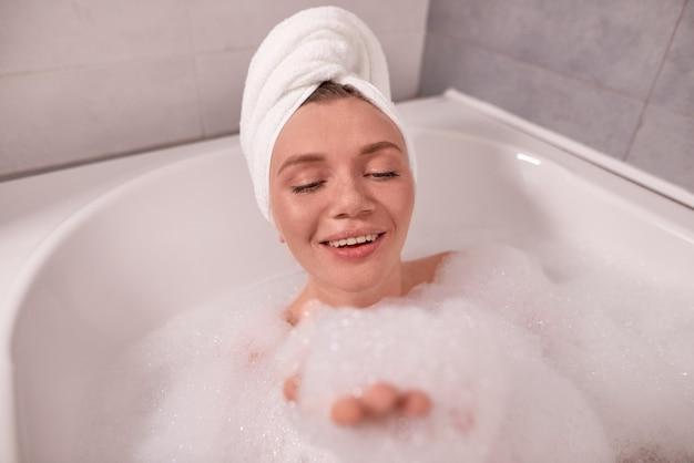 Jonge vrouw met handdoek op hoofd nemen bad met schuim en ontspannen in de spa-badkuip thuis