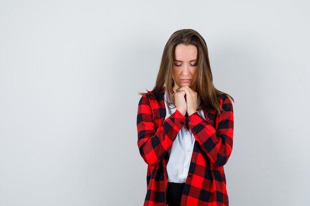 Jonge vrouw met handen in biddend gebaar in vrijetijdskleding en hoopvol, vooraanzicht.