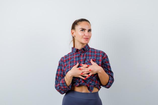 Jonge vrouw met handen met verstrengelde vingers voor haar in geruit hemd, broek en peinzend kijkend. vooraanzicht.